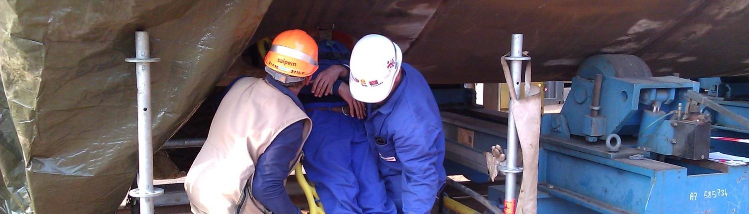 Workers applying first aid to a co-worker