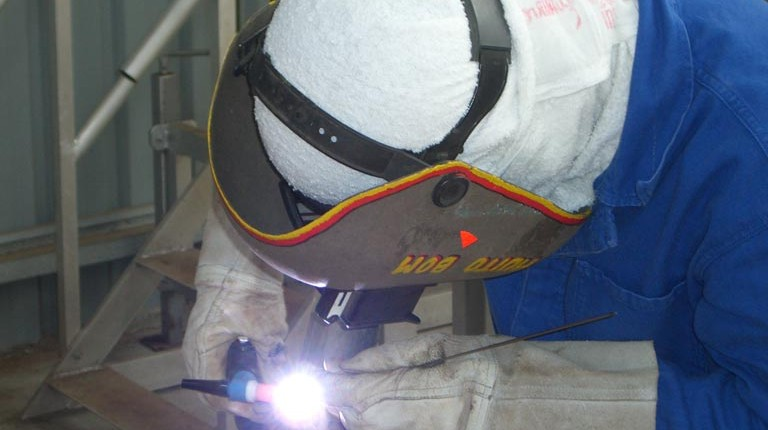 Worker using PPE while working with power tools